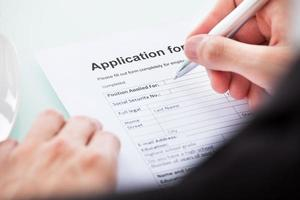 personne remplissant un formulaire à la main photo