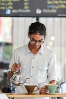 barista brasse une tasse de café dans un café photo
