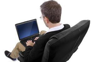 Homme adulte travaillant à la maison sur un ordinateur portable photo