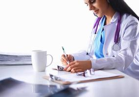 femme médecin, séance bureau, à, papier, et, fonctionnement photo