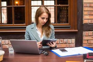 femme d'affaires travaillant dur au restaurant avec ordinateur portable et pad. photo