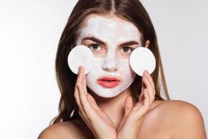 fille avec visage blanc pack et tampons de coton dans les mains photo