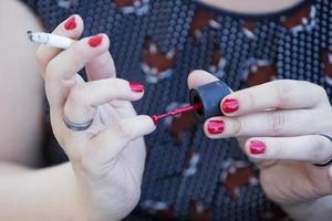 Gros plan de femme mettant du vernis à ongles sur photo