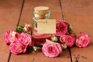 essence de fleurs roses dans une bouteille en verre