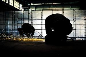 deux ouvriers polissent une partie de la construction en acier photo