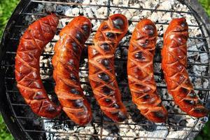 griller des saucisses sur la grille du barbecue photo