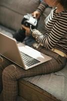 Gros plan sur la femme avec un ordinateur portable à l'aide d'un appareil photo reflex numérique moderne
