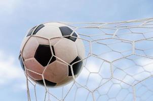 football football dans le filet de but avec le champ de ciel.