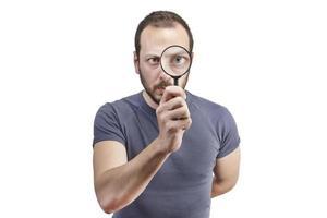 homme étonné regardant à travers une loupe photo