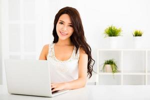 heureuse jolie femme à l'aide d'un ordinateur portable dans le salon