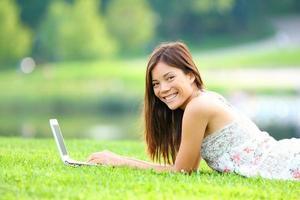 fille dans le parc sur ordinateur portable photo