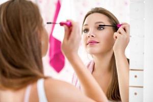 Maquillage femme mettant du rouge à lèvres portant des rouleaux de cheveux se prépare photo