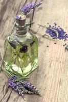 huile essentielle de lavande aux herbes avec des fleurs fraîches photo