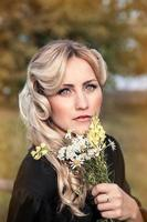 belle femme blonde en robe noire en journée d'été, en plein air