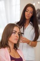 coiffeur faisant coupe de cheveux pour les femmes dans un salon de coiffure. photo