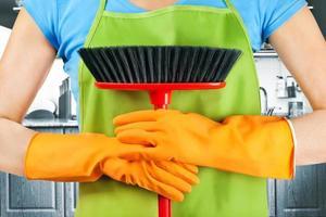 femme de ménage caucasien tenant une brosse de balayage photo