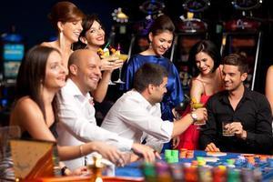 heureux amis caucasiens jouant à la roulette au casino photo