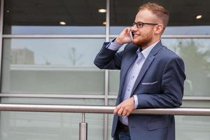 homme d'affaires caucasien à l'extérieur du bureau à l'aide de téléphone portable. photo