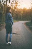 jeune femme caucasienne brune regarder en arrière sur la route photo