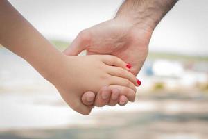 Main d'homme caucasien tenant la main d'un enfant par un lac photo