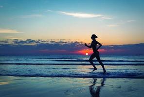 fille courir le long de la côte de la mer photo