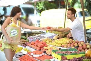 marchand de légumes distribuant un fruit à un consommateur.