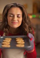 Heureuse jeune femme au foyer appréciant l'odeur des biscuits de Noël sur pan
