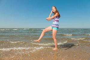 fille heureuse aux longs cheveux bruns profitant de la plage rafraîchissante. photo