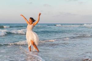 jeune femme bénéficie d'une promenade sur la plage au crépuscule. photo