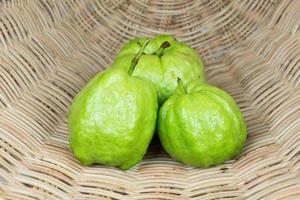 trois fruits de goyave sur fond de rotin