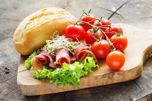 tomates, salade, jambon et pain à une planche à découper photo