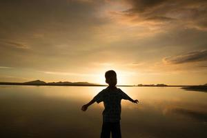 enfant qui profite de la mer au coucher du soleil.