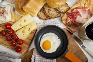 œuf au plat dans la poêle, fromage, jambon, pain et brioches