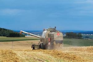 ancienne moissonneuse-batteuse sur le terrain la récolte de blé d'or photo