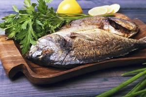 assiette en bois avec deux poissons de carpe rôtie dorado photo