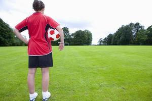 joueur football, à, balle, regarder bas, champ photo