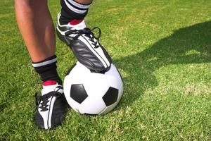 joueur de football avec un ballon de soccer sur le terrain de football photo