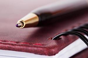 stylo noir et or couché sur un ordinateur portable avec couverture photo