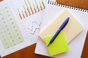 carnet de notes et graphique sur table en bois photo