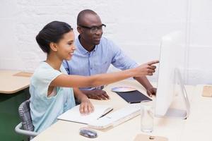 femme montrant quelque chose à son collègue sur l'ordinateur portable