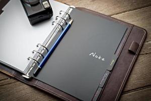 agenda et appareil photo rétro sur une table en bois