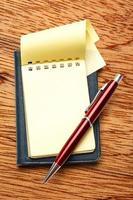 bloc-notes vide jaune avec stylo photo