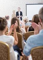 Le public applaudit le professeur après la conférence photo
