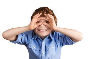 beau garçon souriant fait des lunettes aviateur avec ses mains. isolé photo
