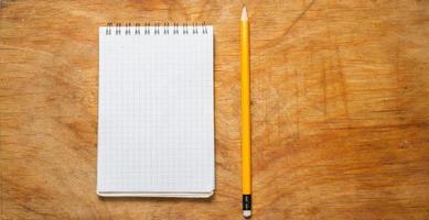 crayon et bloc-notes sur une vieille table rustique. photo