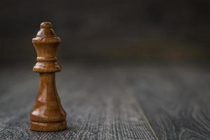 reine noire, pièce d'échecs sur une table en bois photo