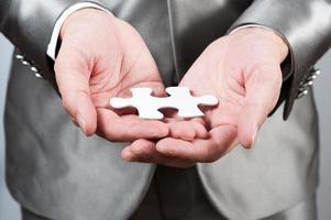 homme d'affaires montrer puzzle blanc à la main, concept de stratégie d'entreprise photo