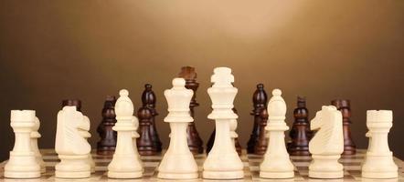échiquier avec pièces d'échecs sur fond marron photo