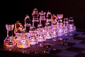 échecs en verre sur l'échiquier éclairé par une lumière bleue et orange photo