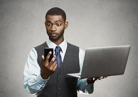 homme affaires, tenue, sien, ordinateur portable, regarder, grand, yeux, téléphone photo